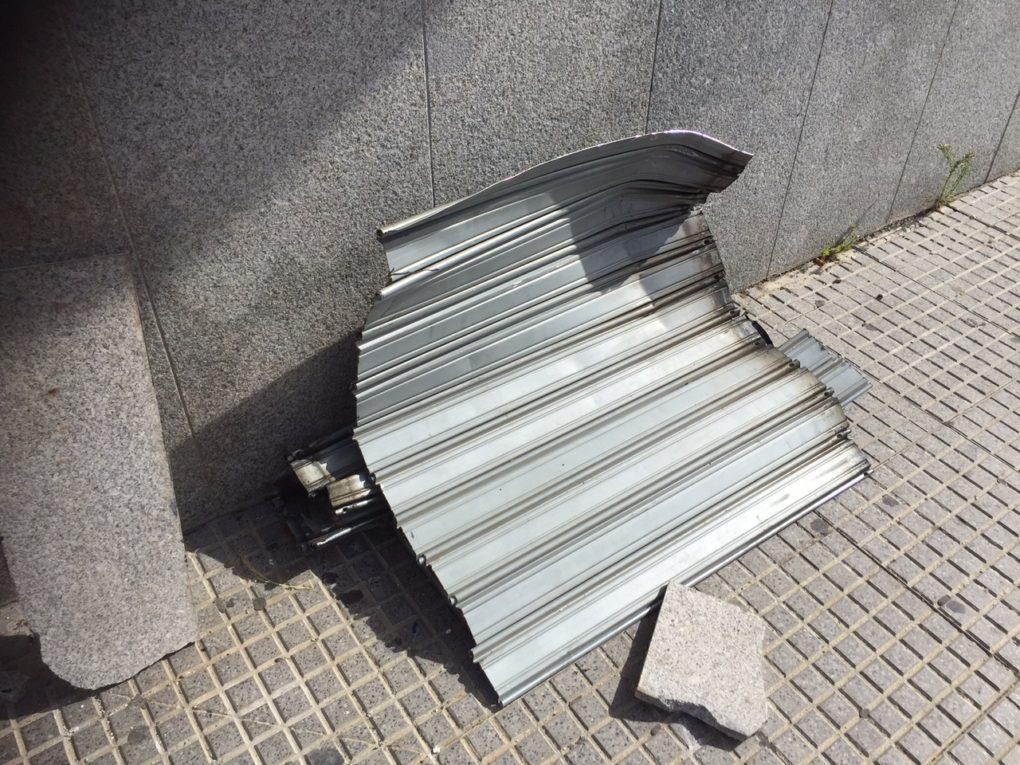 Estado en el que ha quedado la persiana metálica de uno de los establecimientos tras el impacto de un vehículo contra ella